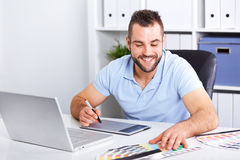 Graphic designer using a graphics tablet in a modern office. Happy graphic designer using a graphics tablet in a modern office royalty free stock photos