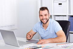 Graphic designer using a graphics tablet in a modern office. Happy graphic designer using a graphics tablet in a modern office Stock Photo