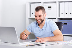 Graphic designer using a graphics tablet in a modern office. Happy graphic designer using a graphics tablet in a modern office Stock Photography