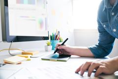 Graphic designer using graphics tablet to do work. At desk stock photos