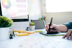 Graphic designer using graphics tablet to do work at desk. Graphic designer using graphics tablet to do work at desk royalty free stock image