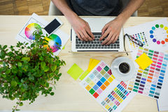 Graphic designer using laptop at his desk Royalty Free Stock Images