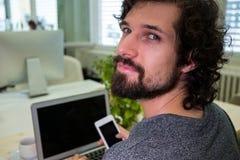 Graphic designer using mobile phone at his desk Stock Photo