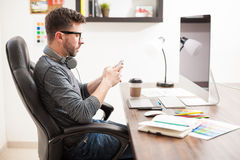 Graphic designer using a smartphone. Profile view of a handsome graphic designer using a smartphone and texting while sitting in front of a computer royalty free stock photo