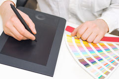 Graphic designer at work. Close up of graphic designer working, with pantone palette and graphic tablet Royalty Free Stock Image
