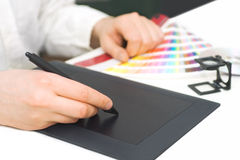Graphic designer at work. Close up of graphic designer working, with pantone palette and graphic tablet stock images