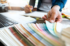 Graphic designer at work with color samples for selection. . Man working with color samples for selection. Graphic designer at work. Color swatch samples royalty free stock image
