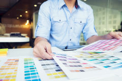 Graphic designer at work. Color swatch samples. Man working with color samples for selection. Graphic designer at work. Color swatch samples royalty free stock photography