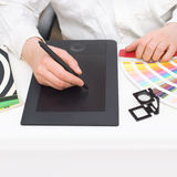 Graphic designer at work. Graphic designer with magazines, magnifier, palette and graphic tablet in front of monitor stock image