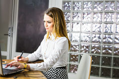 Graphic designer at work. Young female designer using graphics tablet while working with computer stock photo