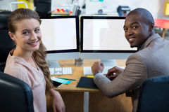 Graphic designer working at desk with colleague. Portrait of graphic designer working at desk with colleague in office stock images