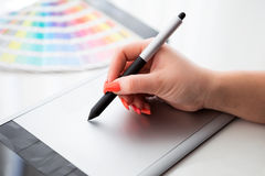 Graphic designer working on a digital tablet and with palette Royalty Free Stock Images