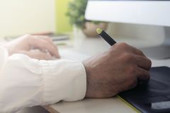 Graphic designer working. With pen tablet stock image