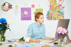Graphic designer wrapped up in work. Concentrated graphic designer creating logo for client while sitting at messy office desk, white wall decorated with flowers royalty free stock photos