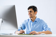 Graphic designer. Young graphic designer sitting at desk and working Stock Images