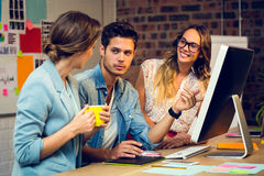 Graphic designers discussing over computer Stock Photos