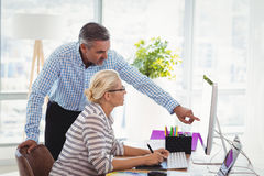 Graphic designers discussing over personal computer at desk. In office Stock Images
