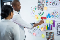 Graphic designers discussing over sticky notes on board Royalty Free Stock Photo