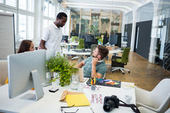 Graphic designers interacting at their desk Stock Image