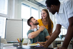 Graphic designers interacting at their desk Royalty Free Stock Photo