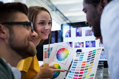 Graphic designers interacting at their desk Stock Photos