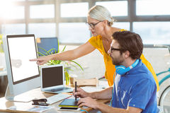 Graphic designers interacting while working on computer Stock Images