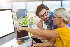 Graphic designers interacting while working on computer Stock Photography