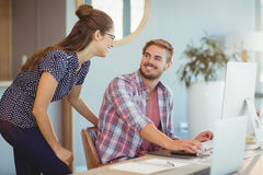 Graphic designers interacting while working on personal computer. In office Stock Photo