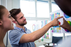 Graphic designers looking at color chart. In office Royalty Free Stock Images