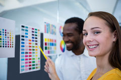 Graphic designers looking at color chart. Portrait of graphic designers looking at color chart in office Royalty Free Stock Photography