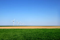Graphic modern landscape of wind turbines aligned in a field. Graphic modern landscape of wind turbines aligned in a green and yellow field Stock Images
