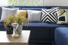 Graphic pattern cushion on blue sofa stock images