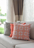 Graphic pattern, orange and gray pillow on beige sofa Stock Images