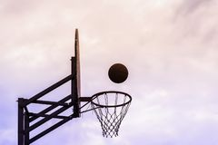 Graphic photo of Basketball shield, ball flying to basket on background of sky. Concept of sport, hit accuracy. Copy royalty free stock photography