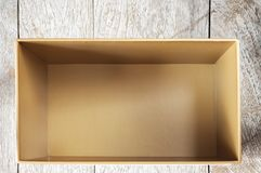 Top view of empty open cardboard box on wooden background Royalty Free Stock Photos