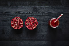 Graphic sliced  pomegranate and red smoothie with straw Stock Images