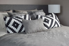 Graphic style and grey shade pillows on classic color bedding. Set up stock photography