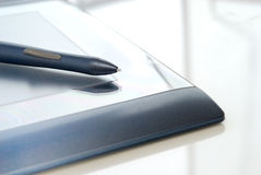 Graphic tablet. A blue graphic tablet with electronic pen on white background Stock Photo