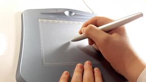 Graphic tablet for drawing. The artist`s hand paints on the surface. Illustrator`s job