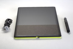 The graphic tablet with a stylus and wires on white background Royalty Free Stock Images