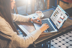 Graphics and diagrams on computer screen. Woman analyzing data. Student learning online. Freelancer working home. Young business woman sitting at table in coffee Stock Images