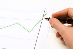 Graphics green lign going up 2. Graphics showing a green lign going up. Someone's hand is holding a pen and is following the lign. Succes. work writing text Royalty Free Stock Images