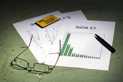 Graphics pen glasses. Image of papers with graphics with a pen, glassen and calculator lying beside. Looks like someone's working Stock Photos