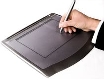 Graphics tablet. Hand holding a graphics pen writing on a tablet stock photos