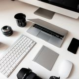Graphics tablet, camera, laptop, black cup, objects, keyboard, mobile phone and wireless mouse on a white wooden table. Concept of the artist Desktop. View royalty free stock image