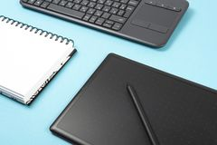 Graphics tablet and keyboard on a blue background. Space for text, notebook royalty free stock photography