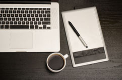 Graphics tablet with a pencil, laptop keyboard and cup of coffee on a black wooden table, close up Stock Photography