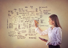 Graphics. Young businesswoman drawing graphics on a white board royalty free stock photo
