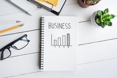 Graphique de buts d'affaires avec le bloc-notes sur la table de bureau avec des approvisionnements Photographie stock libre de droits