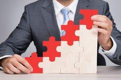 Graphique de Holding Red Jigsaw d'homme d'affaires sur le Tableau photo stock